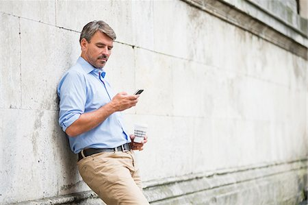 Mature businessman leaning against wall reading texts on smartphone and drinking takeaway coffee Stock Photo - Premium Royalty-Free, Code: 649-07803490