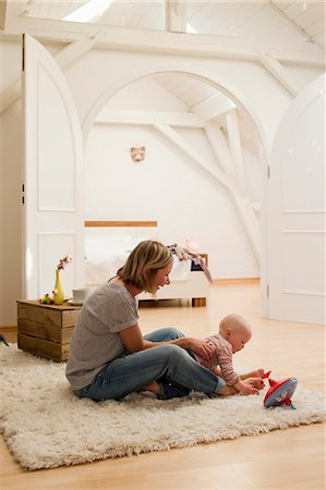 Mature mother and baby daughter playing on rug in sitting room Stock Photo - Premium Royalty-Free, Code: 649-07803563