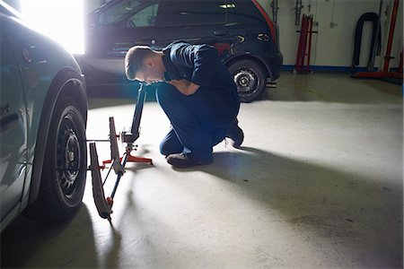 Male student mechanic checking car wheel in college garage Stock Photo - Premium Royalty-Free, Code: 649-07803897