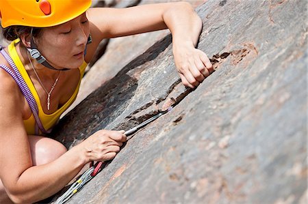"""rock climber - Female climber placing a small nut on """"the Socialist"""", Fairy Cave Quarry Stock Photo - Premium Royalty-Free, Code: 649-07803940"""