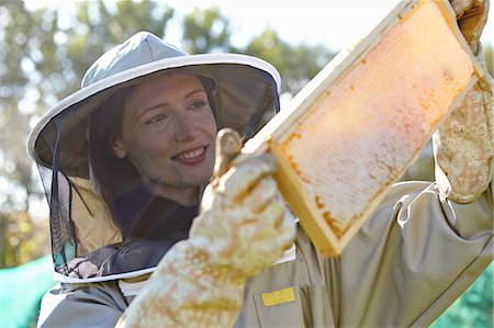 Female beekeepers holding up honeycomb tray on city allotment Stock Photo - Premium Royalty-Free, Code: 649-07803953