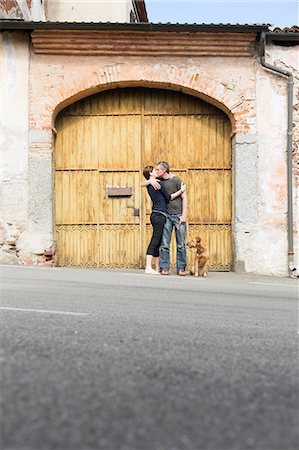 Couple kissing in front of building entrance on street, Suno, Novara, Italy Stock Photo - Premium Royalty-Free, Code: 649-07904980