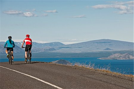 fun happy colorful background images - Cyclists on road next to Thingvallavatn, Langjokull in  background, Thingvellir National Park, South West Iceland Stock Photo - Premium Royalty-Free, Code: 649-07904995