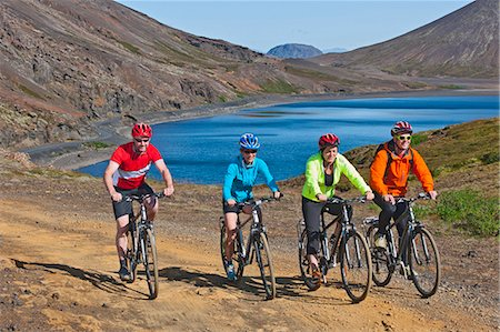 fun happy colorful background images - Cyclists cycling up track, Kleifarvatn in background, Reykjanes, South West Iceland Stock Photo - Premium Royalty-Free, Code: 649-07904993