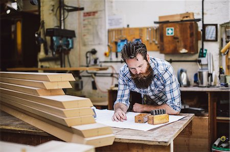 Mid adult craftsman looking down at blueprint in organ workshop Stock Photo - Premium Royalty-Free, Code: 649-07905028