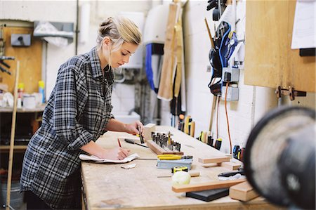 small business - Young craftswoman making notes at workbench in pipe organ workshop Stock Photo - Premium Royalty-Free, Code: 649-07905029