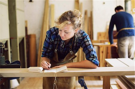 Young craftswoman making notes in pipe organ workshop Stock Photo - Premium Royalty-Free, Code: 649-07905021