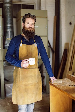 Portrait of mid adult craftsman drinking coffee in organ workshop Stock Photo - Premium Royalty-Free, Code: 649-07905023