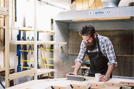 Cropped shot of mid adult craftsman using digital tablet in organ workshop Stock Photo - Premium Royalty-Free, Code: 649-07905036