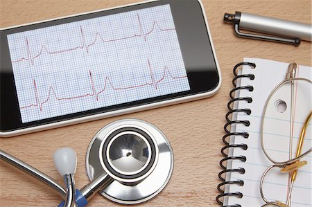 results - Technology use in healthcare. Smartphone displays an electrocardiogram, acoustic stethoscope, notepad, spectacles and pen on doctors office desk Stock Photo - Premium Royalty-Free, Code: 649-07905073