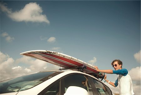 Teenage boy putting surfboard on top of car Stock Photo - Premium Royalty-Free, Code: 649-07905196