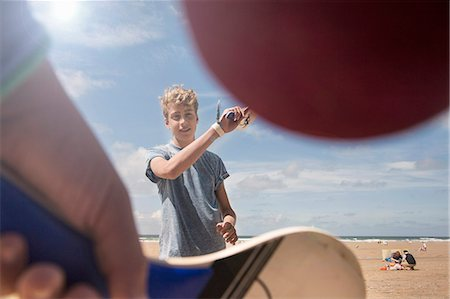 Teenage boy playing bat and ball on beach Stock Photo - Premium Royalty-Free, Code: 649-07905204
