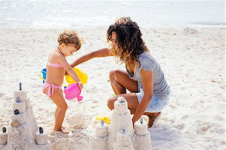 Mother and toddler daughter building sandcastle on beach, Tuscany, Italy Stock Photo - Premium Royalty-Free, Code: 649-07905247