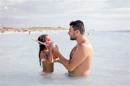 Father teaching daughter how to snorkel in sea, Tuscany, Italy Stock Photo - Premium Royalty-Free, Code: 649-07905256