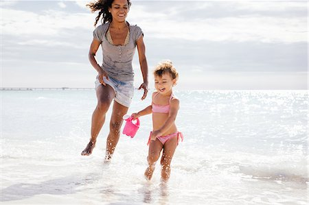 Mother and toddler daughter running with toy watering can on beach, Tuscany, Italy Stock Photo - Premium Royalty-Free, Code: 649-07905250