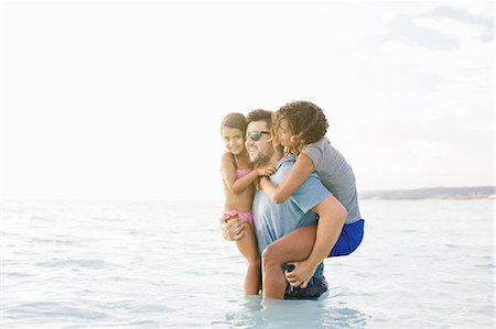 Young man wading in sea carrying wife and daughter, Tuscany, Italy Stock Photo - Premium Royalty-Free, Code: 649-07905274