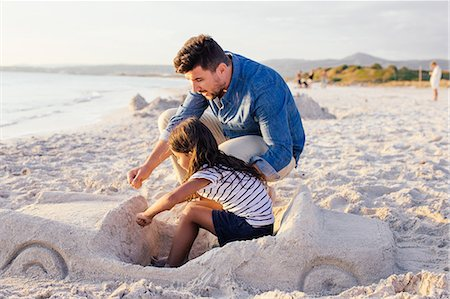 families playing on the beach - Girl and father with sophisticated car sandcastle on beach, Tuscany, Italy Stock Photo - Premium Royalty-Free, Code: 649-07905278