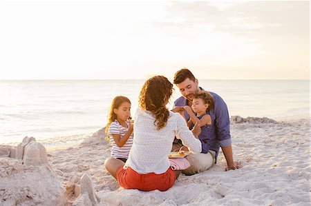 Couple with two girls picnicing with cakes on beach, Tuscany, Italy Stock Photo - Premium Royalty-Free, Code: 649-07905281