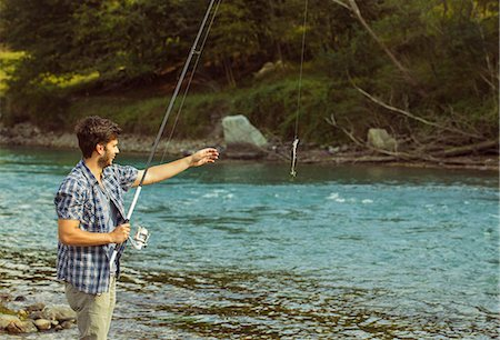 fishing - Young man catching fish in river, Premosello, Verbania, Piemonte, Italy Stock Photo - Premium Royalty-Free, Code: 649-07905335