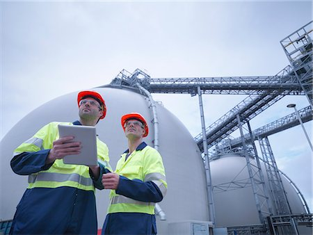 science & technology - Workers using digital tablet at biomass facility, low angle view Stock Photo - Premium Royalty-Free, Code: 649-07905376