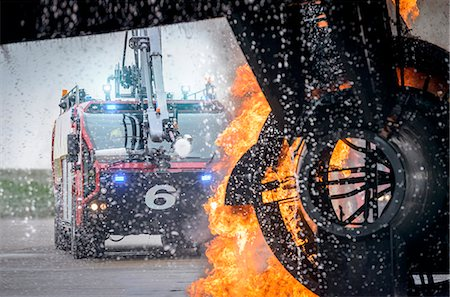 fire - Fire engine spraying water on simulated fire at airport training facility Stock Photo - Premium Royalty-Free, Code: 649-07905588