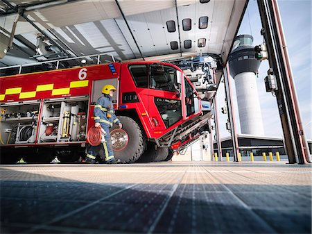 property release - Fireman carrying equipment to fire engine in airport fire station Stock Photo - Premium Royalty-Free, Code: 649-07905580