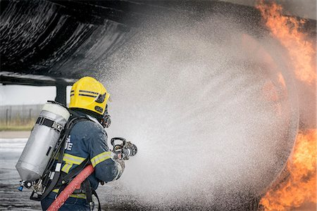 fire - Fireman spraying water on simulated aircraft fire at training facility Stock Photo - Premium Royalty-Free, Code: 649-07905591