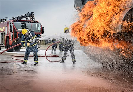 security - Firemen spraying water on simulated aircraft fire at training facility Stock Photo - Premium Royalty-Free, Code: 649-07905593