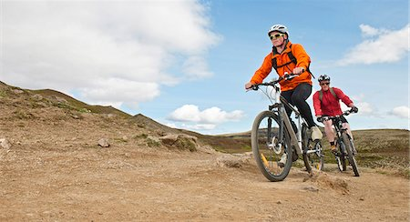people mountain biking - Two young male mountain bikers cycling up dirt track,  Reykjadalur valley, South West Iceland Stock Photo - Premium Royalty-Free, Code: 649-07905687