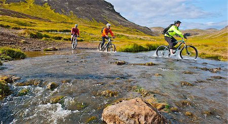 people and vacation - Three mountain bikers cycling through hot river,  Reykjadalur valley, South West Iceland Stock Photo - Premium Royalty-Free, Code: 649-07905698