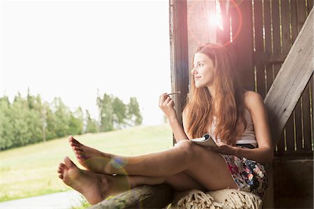 femininity - Young woman sitting in barn with notebook Stock Photo - Premium Royalty-Free, Code: 649-07905745
