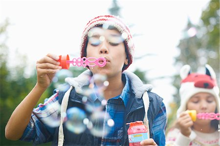 pucker - Siblings blowing bubbles in garden Stock Photo - Premium Royalty-Free, Code: 649-08004035