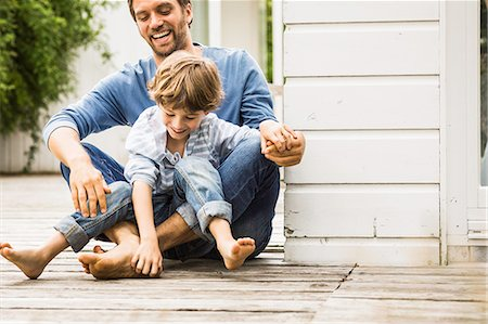 Mid adult man and son laughing and tickling feet on porch Stock Photo - Premium Royalty-Free, Code: 649-08004069