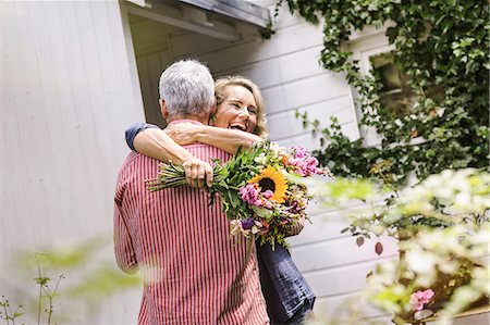 Wife holding bunch of flowers and hugging husband Stock Photo - Premium Royalty-Free, Code: 649-08004099