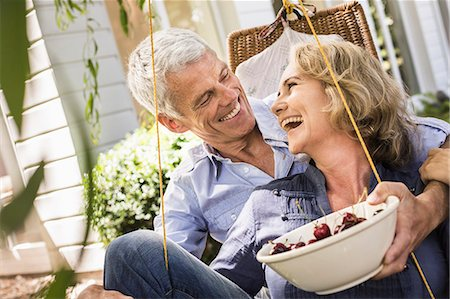 Husband and wife relaxing with bowl of cherries on hammock Stock Photo - Premium Royalty-Free, Code: 649-08004114