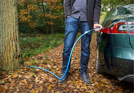 Man charging electric car in forest Stock Photo - Premium Royalty-Free, Code: 649-08004126