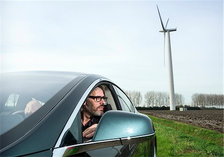 Man in car with wind turbine in background Stock Photo - Premium Royalty-Free, Code: 649-08004128