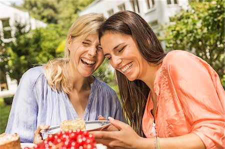 Two female friends in garden, laughing, holding plate with dessert Stock Photo - Premium Royalty-Free, Code: 649-08004191