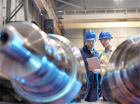 people working in factory - Engineers inspecting finished steel rollers in engineering factory Stock Photo - Premium Royalty-Free, Code: 649-08004201