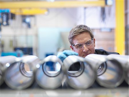 Engineer inspecting steel parts in factory Stock Photo - Premium Royalty-Free, Code: 649-08004257