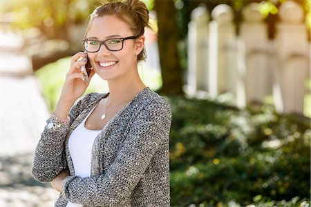 Portrait of young woman in park chatting on smartphone Stock Photo - Premium Royalty-Free, Code: 649-08004412