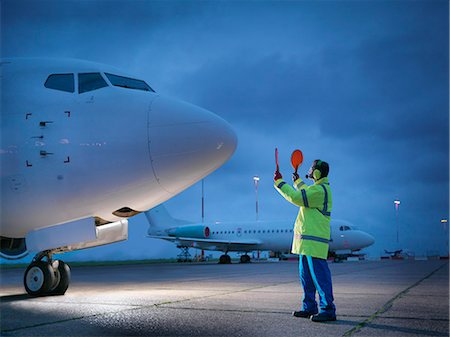 security - Airport worker guiding aircraft on runway at night Stock Photo - Premium Royalty-Free, Code: 649-08004436