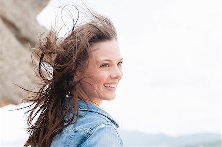 summer - Mid adult woman at coast with hair blowing in breeze, Sardinia, Italy Stock Photo - Premium Royalty-Free, Code: 649-08003924