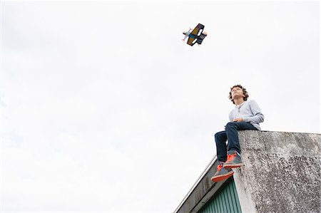 Boy sitting on garage roof, flying remote controlled plane Stock Photo - Premium Royalty-Free, Code: 649-08003949