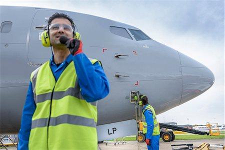 Airside engineer talking on radio near aircraft on runway Stock Photo - Premium Royalty-Free, Code: 649-08060075
