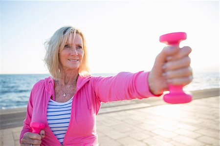 Senior woman exercising with weights by beach Stock Photo - Premium Royalty-Free, Code: 649-08060121