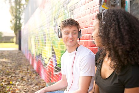 Teenage couple listening to mp3 player against wall with graffiti Stock Photo - Premium Royalty-Free, Code: 649-08060281