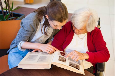 Mid adult woman and her grandmother pointing and looking at photograph album Stock Photo - Premium Royalty-Free, Code: 649-08060313