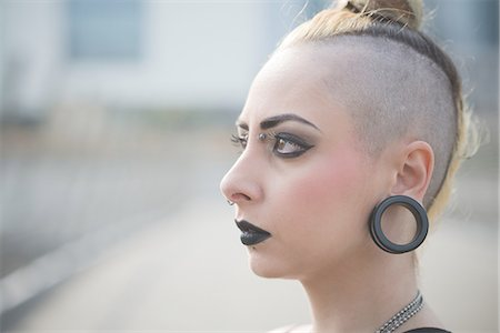 Portrait of young female punk with earlobe piercing and shaved head Stock Photo - Premium Royalty-Free, Code: 649-08060329
