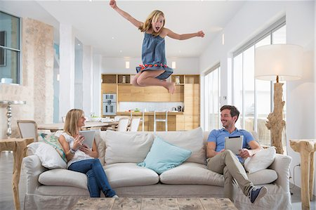Girl jumping mid air from living room sofa whilst parents use digital tablet Stock Photo - Premium Royalty-Free, Code: 649-08060389